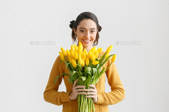 Woman with tulips. Young brunette girl with yellow flowers tulip - Stock Photo - Images
