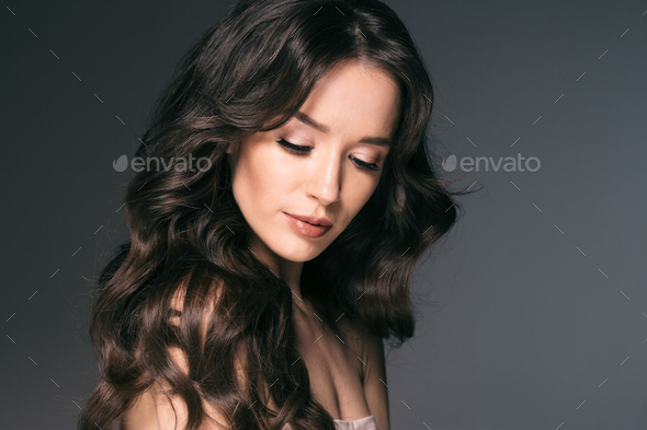 Beautiful woman with long hair, shine and curly, beauty girl female over darl gray background - Stock Photo - Images