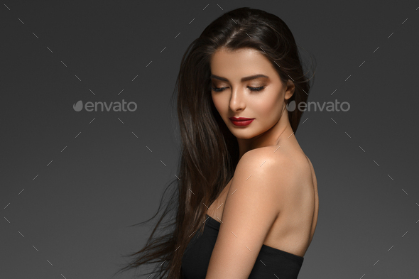 Beautiful woman with long brunette smooth beauty hair over dark backgroun. - Stock Photo - Images
