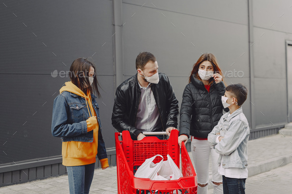 Family in protective masks with purchases - Stock Photo - Images