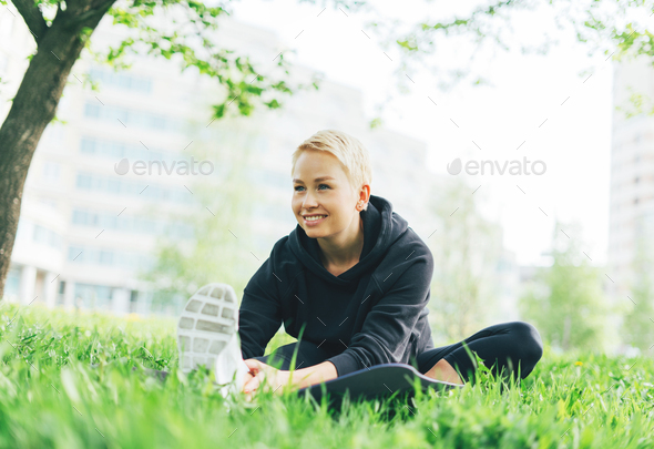 Attractive fit young woman in sport wear stretching on green grass in city park - Stock Photo - Images