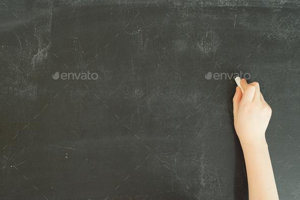 child's hand holding white chalk on black chalkboard background - Stock Photo - Images