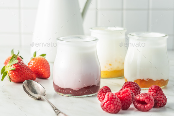 White fruity yogurt in jar and raspberries. - Stock Photo - Images