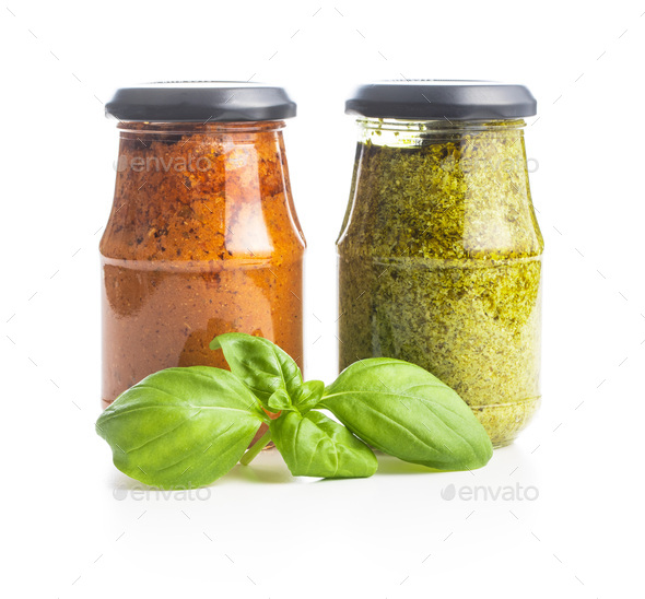 Green basil and red tomato pesto dip sauce in jar and basil leaves. - Stock Photo - Images