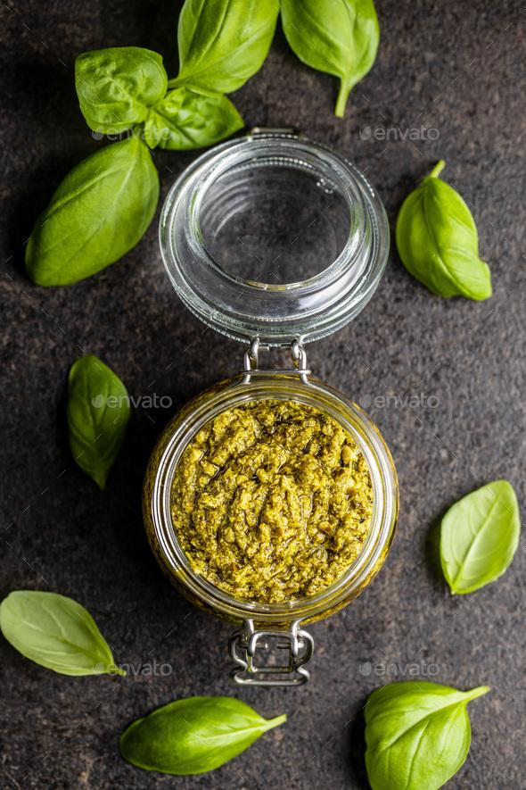 Green basil pesto dip sauce and basil leaves. - Stock Photo - Images