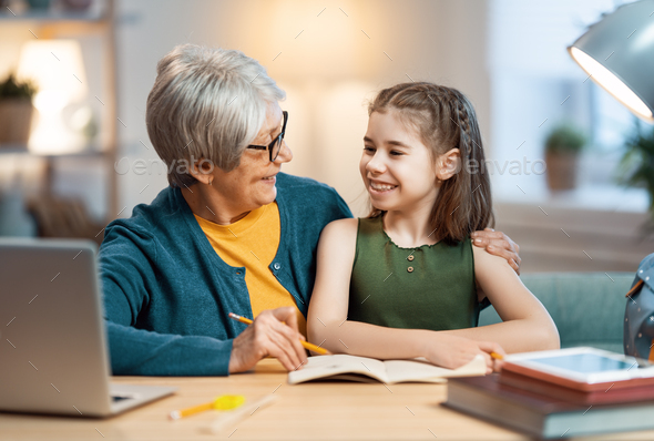 Girl studying with grandma. - Stock Photo - Images