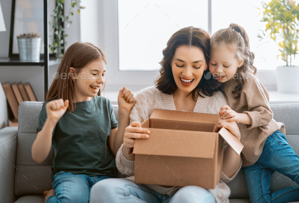 Mother and daughters are unpacking cardboard - Stock Photo - Images