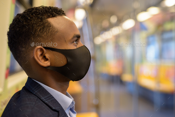 Face of young African businessman with mask for protection from corona virus outbreak sitting with - Stock Photo - Images