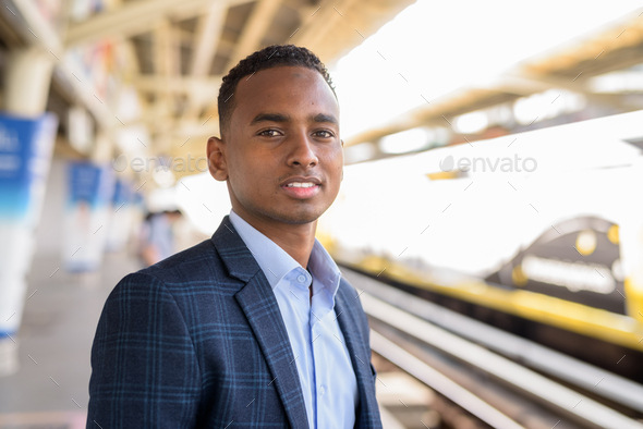 Happy young handsome African businessman smiling while waiting at the sky train station - Stock Photo - Images