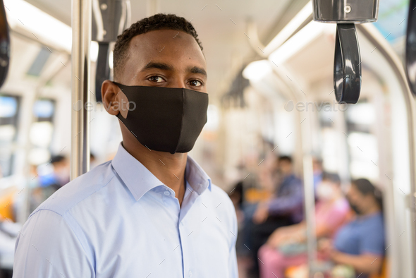 Young African businessman with mask for protection from corona virus outbreak standing with distance - Stock Photo - Images