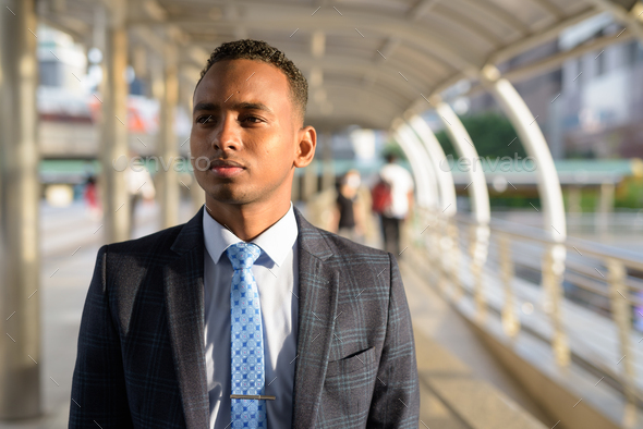 Young handsome African businessman wearing suit thinking in the city - Stock Photo - Images