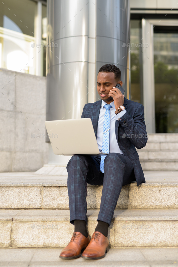 Full body shot of young African businessman using phone and laptop while working outdoors - Stock Photo - Images