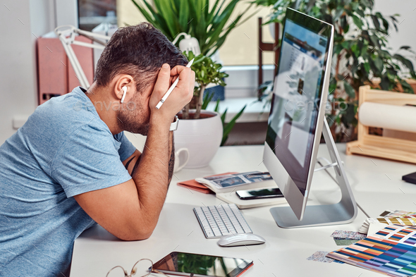 Man feels tired while working in office - Stock Photo - Images