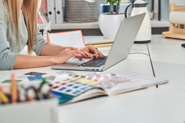 Woman with manicure is typing on laptop - Stock Photo - Images