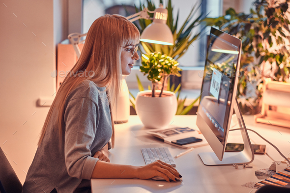 Attractive woman is working on computer - Stock Photo - Images