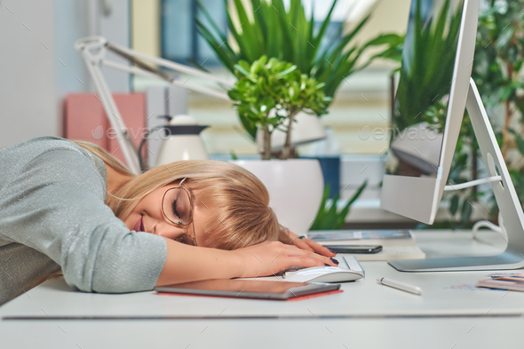 Woman is tired while working in office - Stock Photo - Images