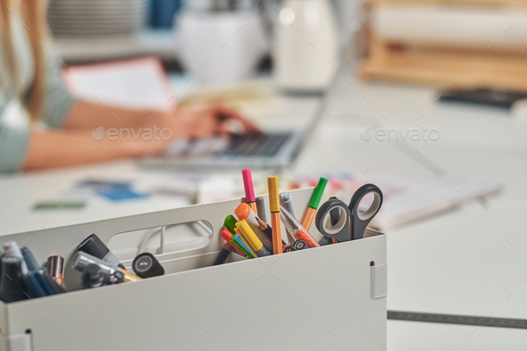 Box with office accesories and woman on the background - Stock Photo - Images