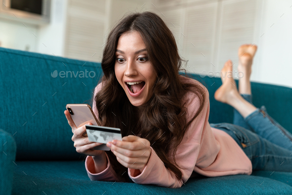 Woman using mobile phone holding credit card on sofa. - Stock Photo - Images