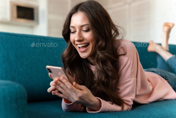 Cheerful young woman indoors at home using phone - Stock Photo - Images