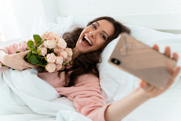 Pretty young woman in bed holding flowers. - Stock Photo - Images