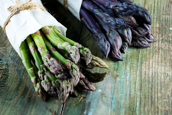 Fresh natural organic two bundles of green and purple asparagus vegetables on a wooden background - Stock Photo - Images