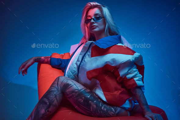 Blond woman is sitting on bean bag - Stock Photo - Images