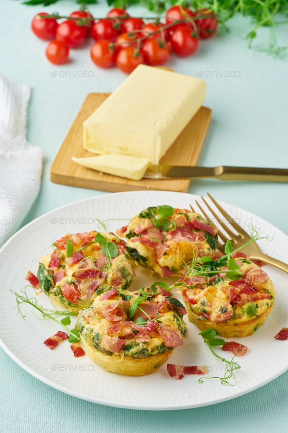 Egg muffin baked with bacon and tomato, ketogenic keto diet, pastel modern closeup vertical - Stock Photo - Images
