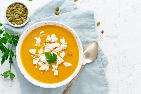 Pumpkin cream soup with feta cheese, autumn homemade food, white background, top view, copy space - Stock Photo - Images