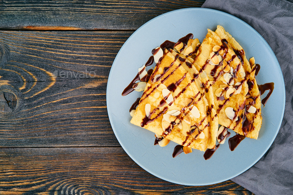 Two pancakes with chocolate syrup, almond flakes on plate, honey flows from spoon - Stock Photo - Images