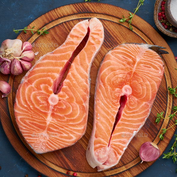 Two salmon steaks, fish fillet, large sliced portions on chopping board - Stock Photo - Images