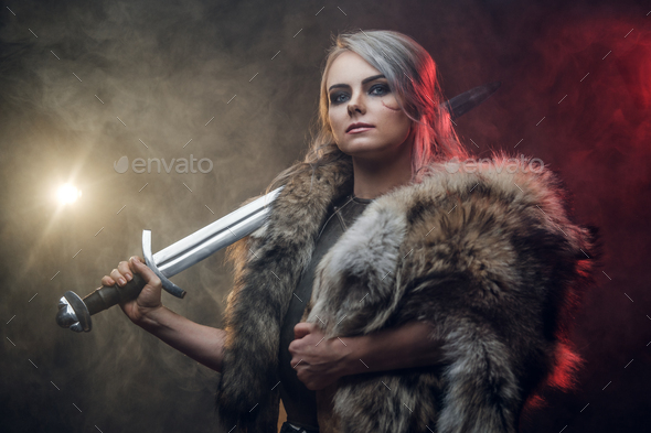 Portrait of a beautiful warrior woman holding a sword wearing steel cuirass and fur - Stock Photo - Images