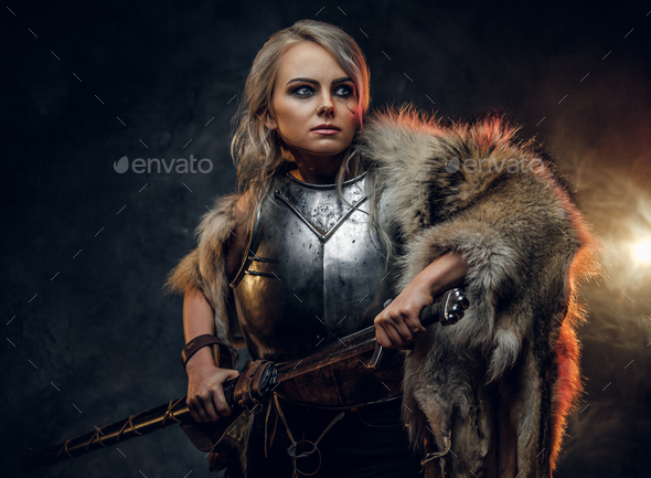Fantasy woman knight wearing cuirass and fur, holding a sword - Stock Photo - Images