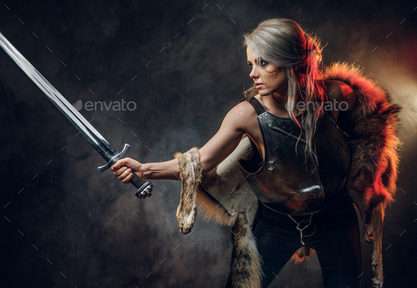 Portrait of a beautiful warrior woman holding a sword wearing steel cuirass and fur. Fantasy fashion - Stock Photo - Images