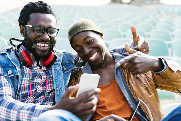 Two black race friends having fun with mobile. - Stock Photo - Images