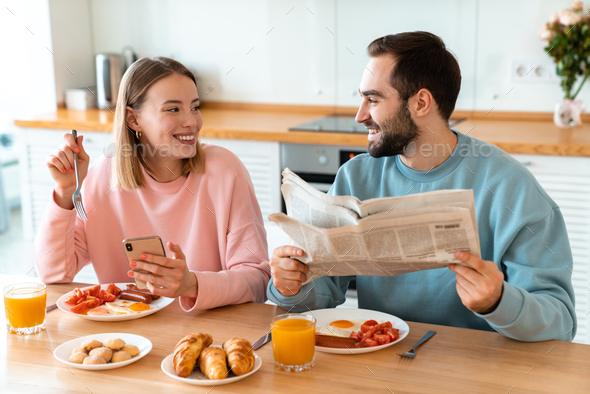 Portrait of joyful couple using cellphone and reading newspaper - Stock Photo - Images