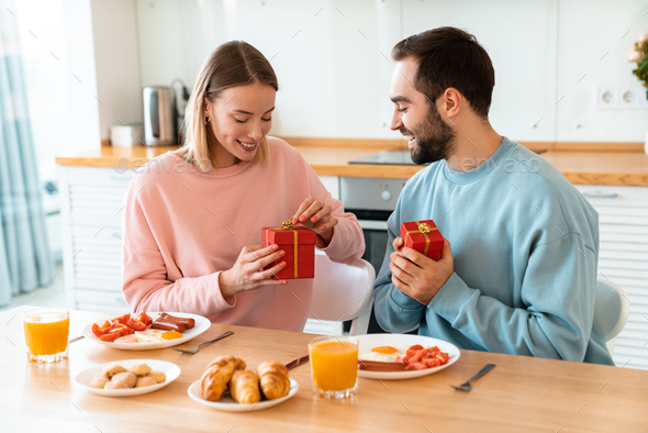 Portrait of happy couple holding gift boxes while having breakfast - Stock Photo - Images