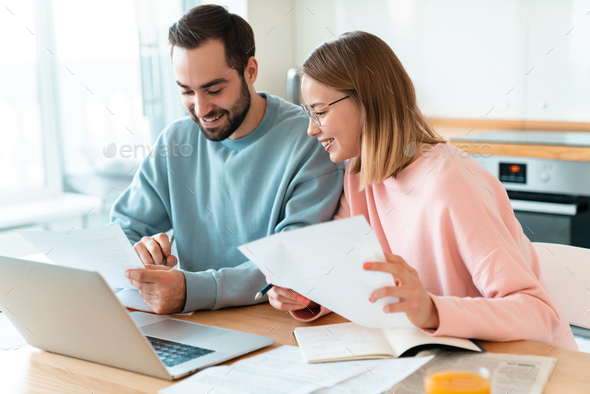 Portrait of young happy couple working with laptop and documents - Stock Photo - Images