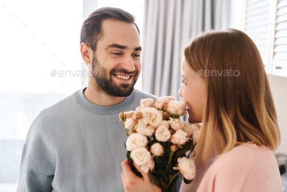 Portrait of cheerful man giving his smiling girlfriend flower bouquet - Stock Photo - Images