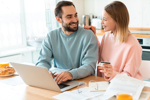 Portrait of happy couple using credit card while working with laptop - Stock Photo - Images