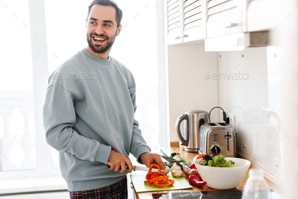 Image of pleased handsome man smiling and making lunch - Stock Photo - Images