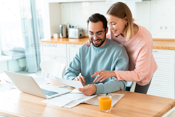 Portrait of young smiling couple working with laptop and documents - Stock Photo - Images