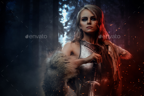 Beautiful warrior woman holding a sword wearing steel cuirass and fur in night forest - Stock Photo - Images