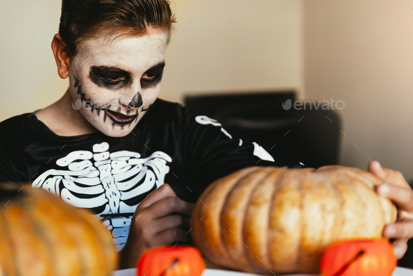 Happy boy disguised decorating a pumpkin at home. - Stock Photo - Images