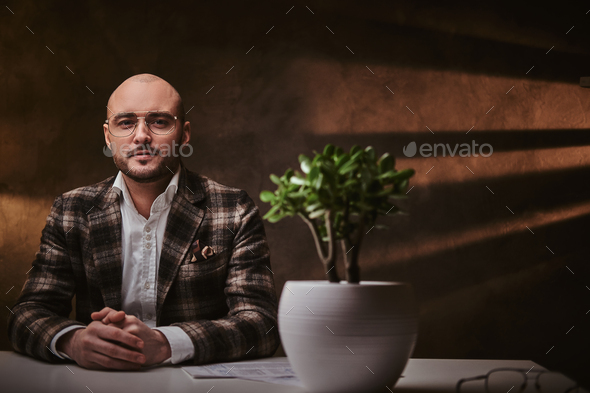 Bald serious thinking european well-dressed businessman sitting in the office - Stock Photo - Images
