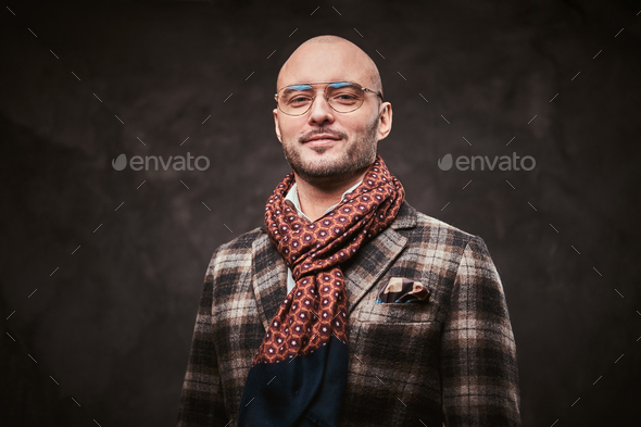 Succesful stylish businessman posing in a studio wearing checkered jacket, glasses and scarf - Stock Photo - Images