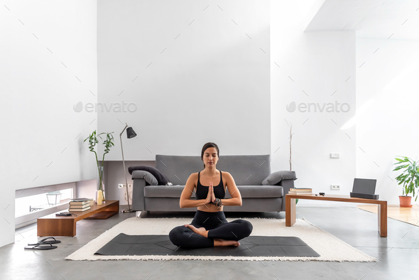 Attractive woman practicing yoga lotus pose to meditation at cozy home - Stock Photo - Images