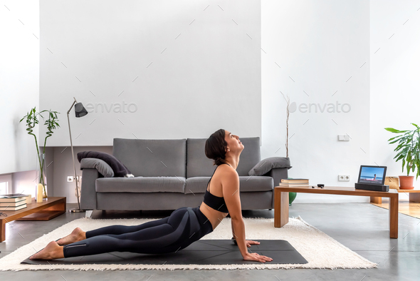 Fit woman practicing Cobra pose using online yoga training program in the tablet at home - Stock Photo - Images