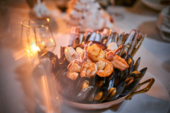 A bowl of grilled shrimps and mussels served on a stone table next to golden candle in a restaurant - Stock Photo - Images
