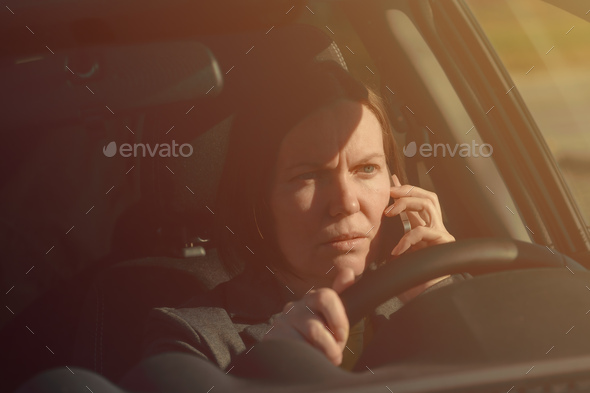 Businesswoman talking on mobile phone in the car - Stock Photo - Images