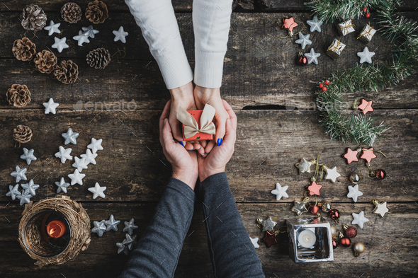 Top view of a male hands cupping female hands holding small red holiday gift box - Stock Photo - Images